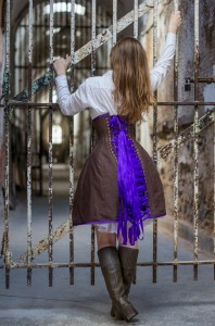 Model in a corset dress posing in front of a rusted gate